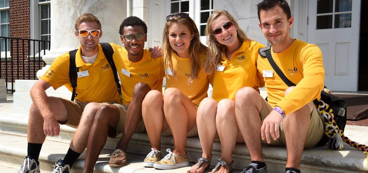four orientation staff students wearing yellow shirts sit on steps with arms around each other