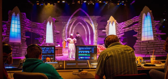 student performers practice Dracula on stage as tech students look on
