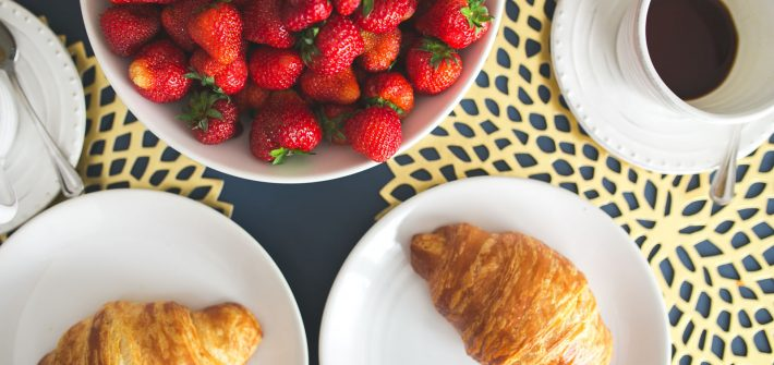 bowl of strawberries and croissants on a kitchen table