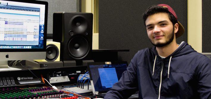 student sits at soundboard