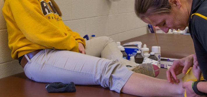 athletic training major works on a student's ankle