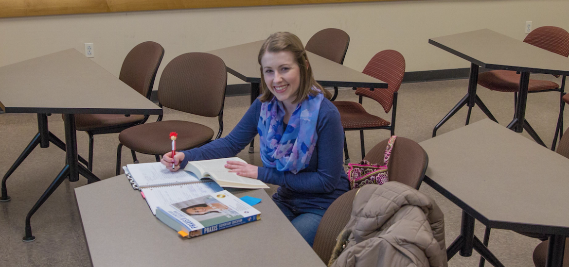student preps for exam sitting at a table