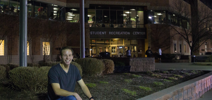 student sits outside rec center
