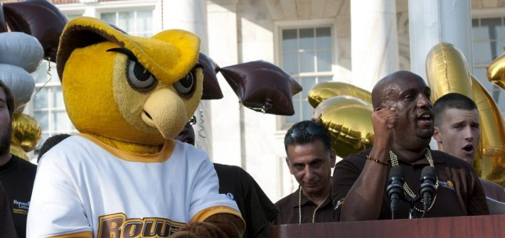 Rowan mascot on stage in front of Bunce to welcome students, surrounded by students