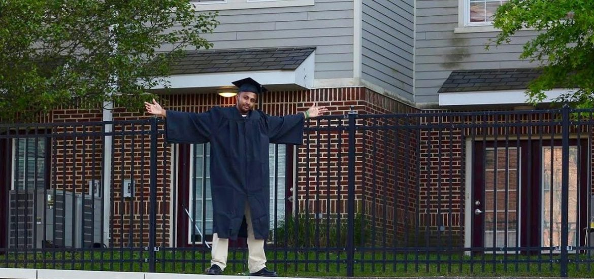 Sha stands in his cap and gown with arms outstretched on top of a Rowan sign
