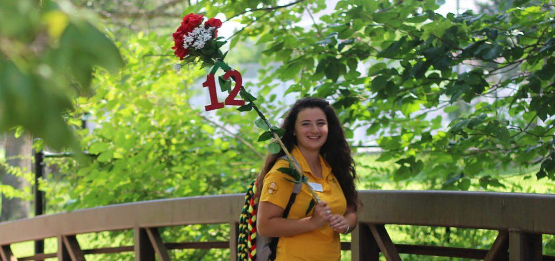standing on bridge holding 12 sign