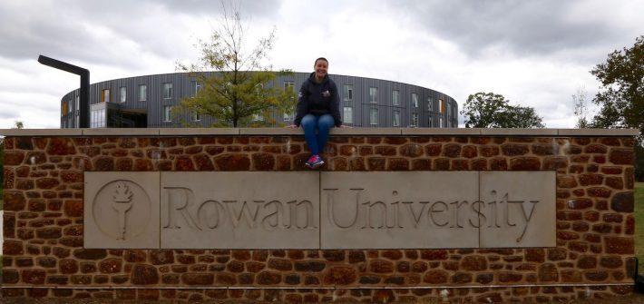 Jereca sitting on Rowan University brick sign outside of Holly Pointe