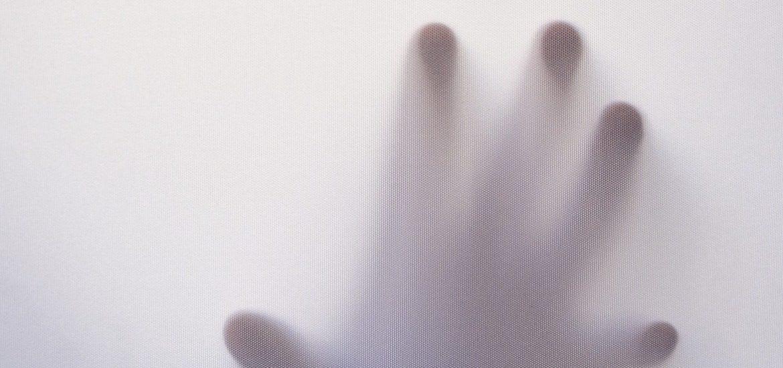 spooky hand reaches out through a white mist