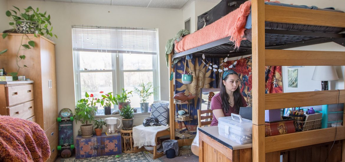 Noel sits at desk in her room in Willow Hall at Rowan University