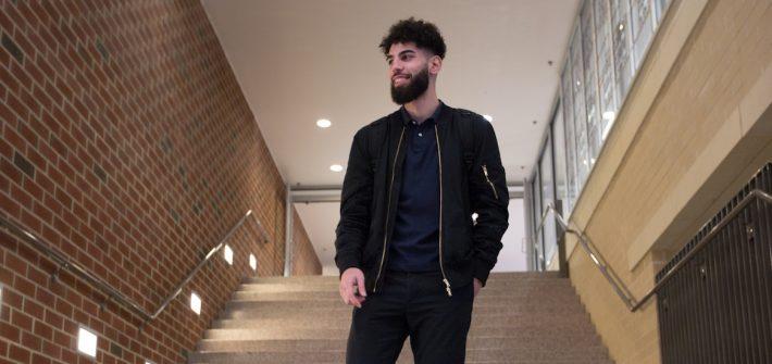 Nabil walks down the stairs in James Hall at Rowan University