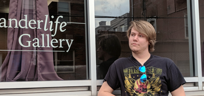 Justin stands next to the glass storefront of Wanderlife Gallery