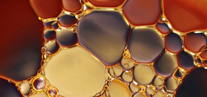 close up of amber colored bubbles in water