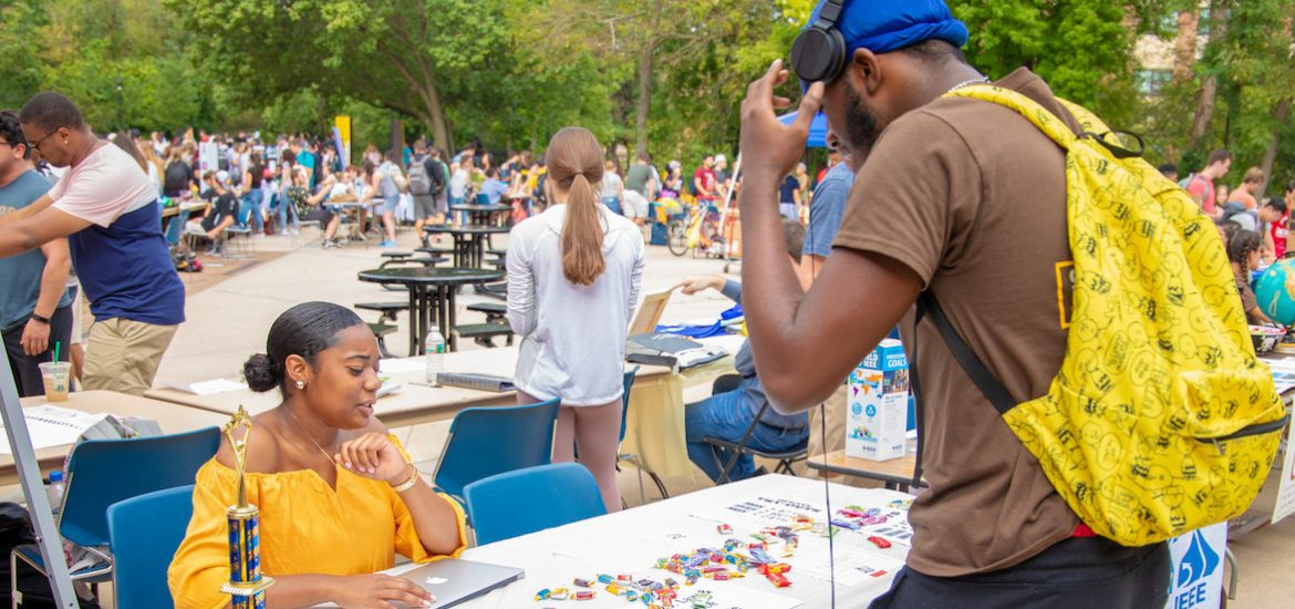 two students chatting about a club over candy at the organization fair