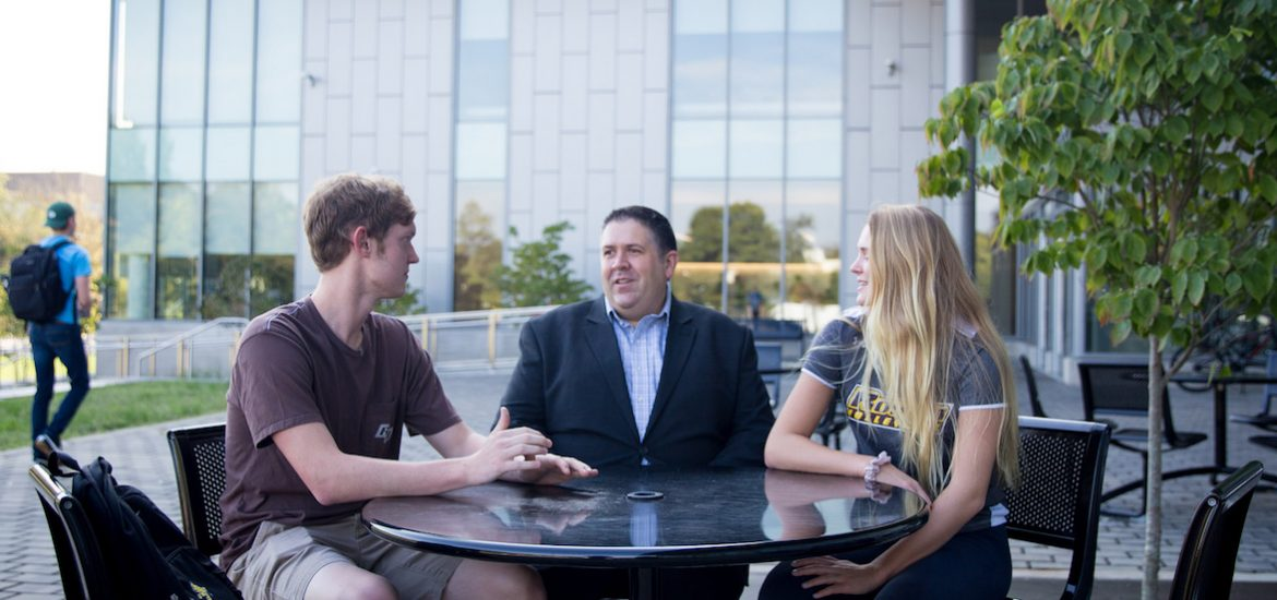 Eric Liguori sitting outside with two students outside the Rohrer College of Business