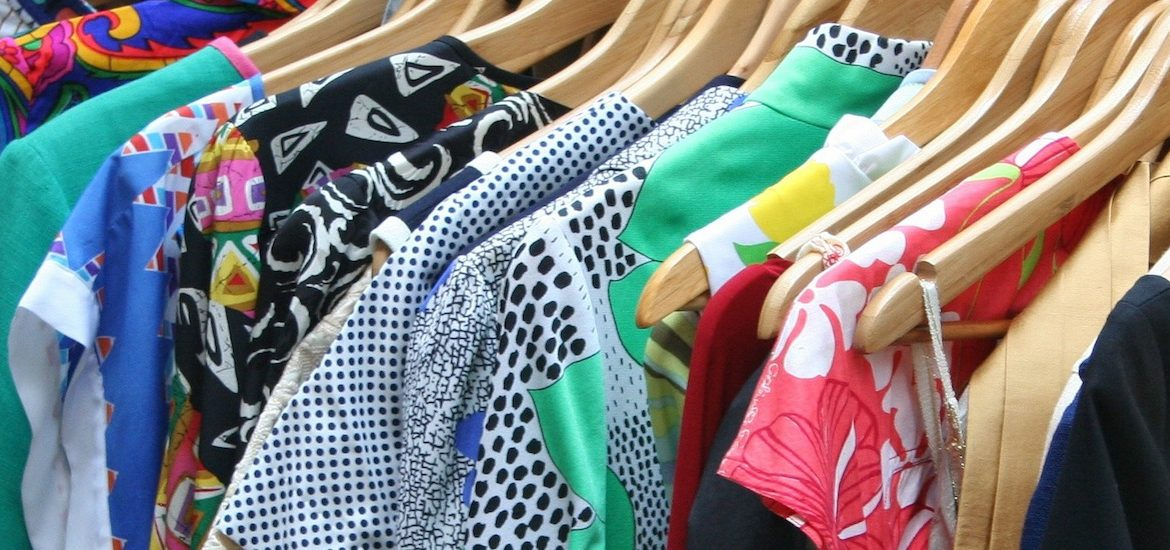 close up of shirts with variety of patterns and colors hanging on hangers in a closet