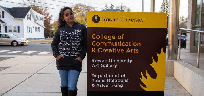Aysha outside College of Communication and Creative Arts sign