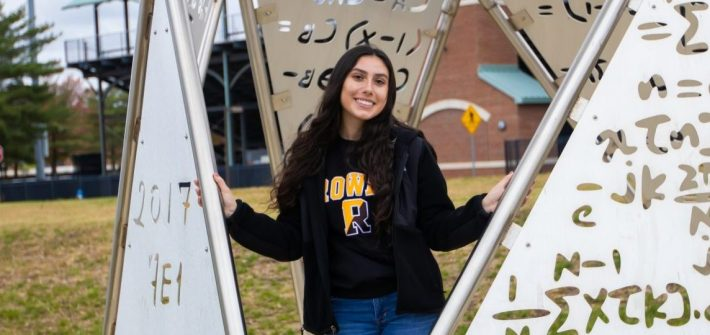 Marcella stands by a metal sculpture outside the Engineering Hall at Rowan University.