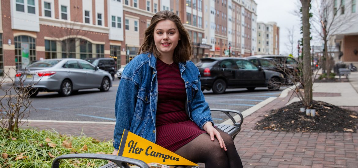 Rachel outside Barnes and Nobles sitting on bench with her books and Her Campus pennant