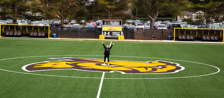 Kylie standing on soccer field, picture taken from bleachers