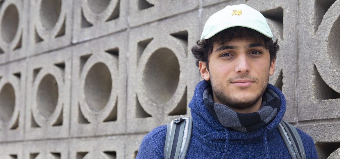 Jacks stands in front of a a wall with a circular concrete pattern, wearing a blue sweatshirt, backpack and Rowan hat