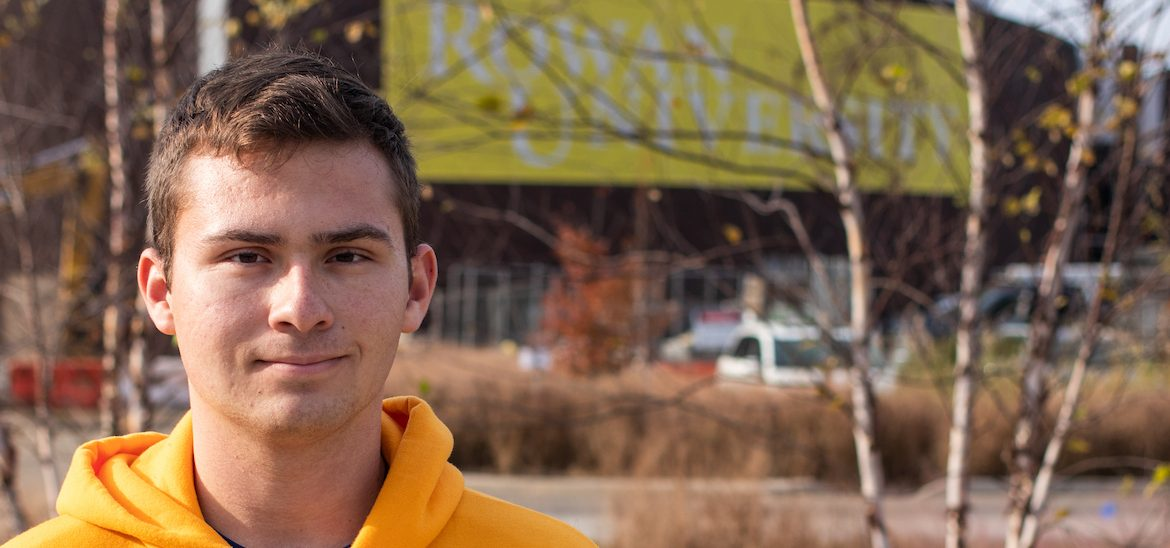 Young, white male student with yellow Rowan University standing in foreground with brick building blurred out in background