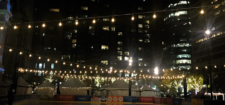 Photo of string lights above City Halls ice skating rink.