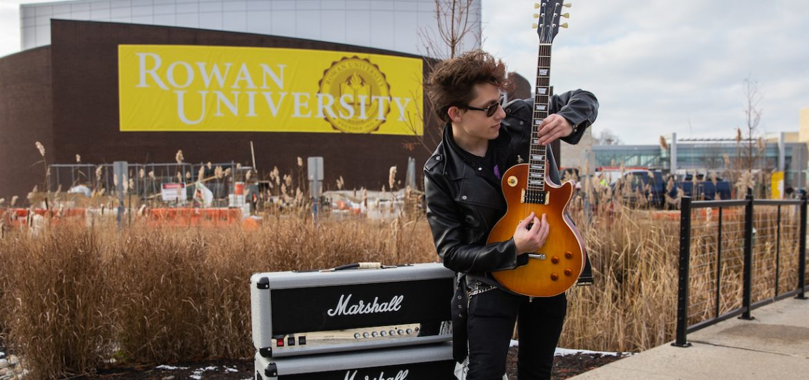 Luke outfront of Wilson Hall with his guitar and amp outfront Rowan University sign