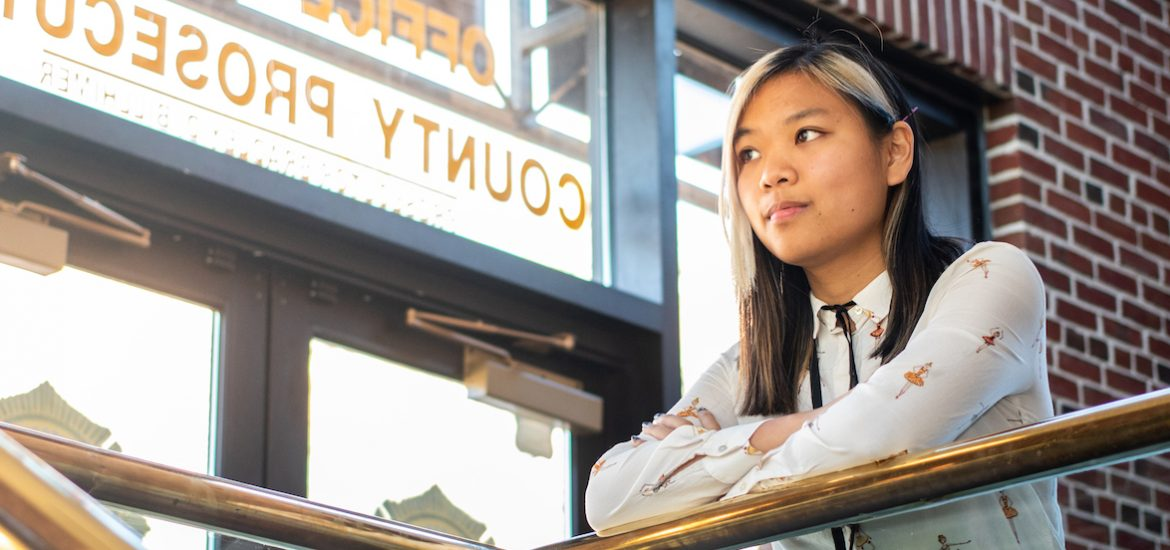 Young lady leaning against hand rail looking off into the distance thinking of all the possibilities the world offers in white button down shirt