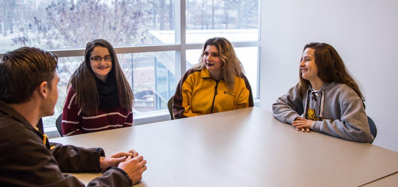 Liz and her friends sitting upstairs in Savitz hall by a snowy window