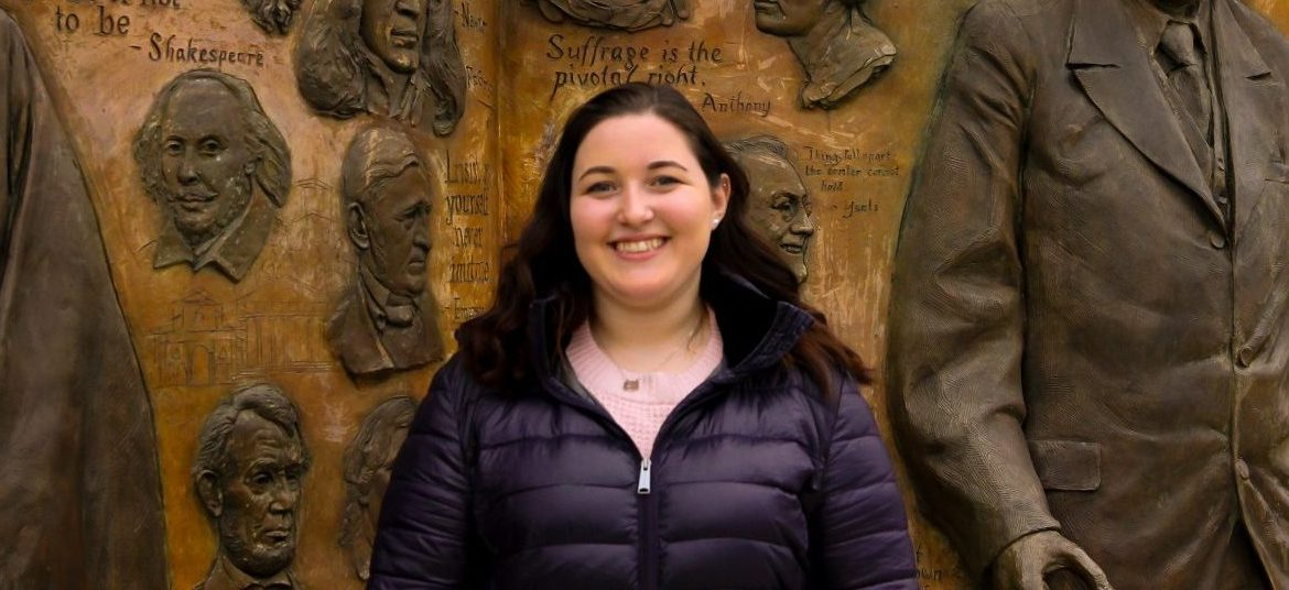 Rebecca Shnier stands outside of James Hall at Rowan University, in front of a bronze artwork that says Knowledge is Power