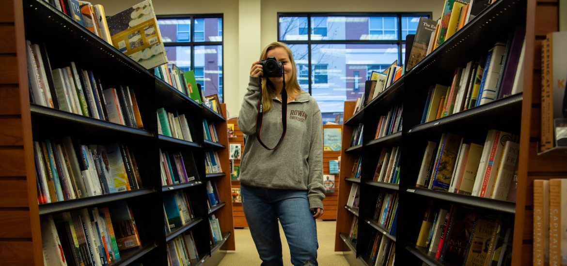 student inside Barnes and Nobles on campus in book aisle taking a photo