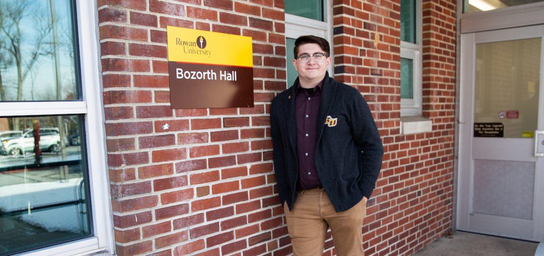 Brandon outside Bozarth Hall in Rowan sweater, in front of brick wall