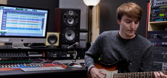 Young male student playing electric guitar inside a music production student while sitting down in a chair