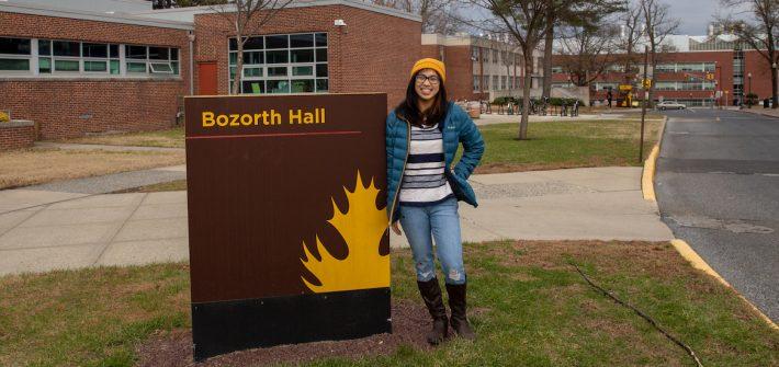 Student Jessica outside Bozorth Hall sign at Rowan University at Glassboro