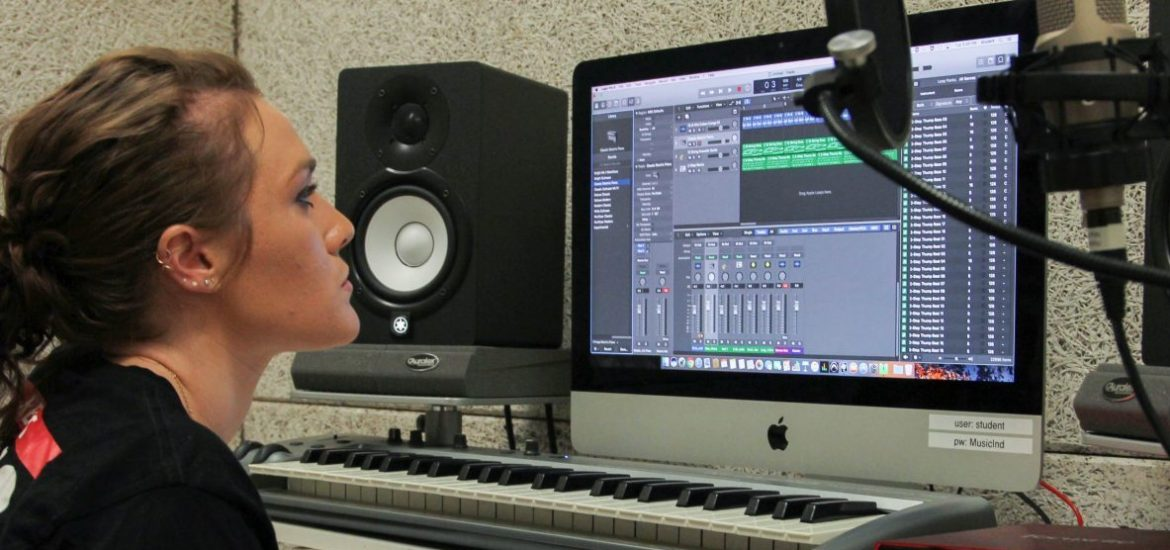 Claire sits at a table with a Mac computer and microphone to work on a song in Wilson Hall's private recording studio.