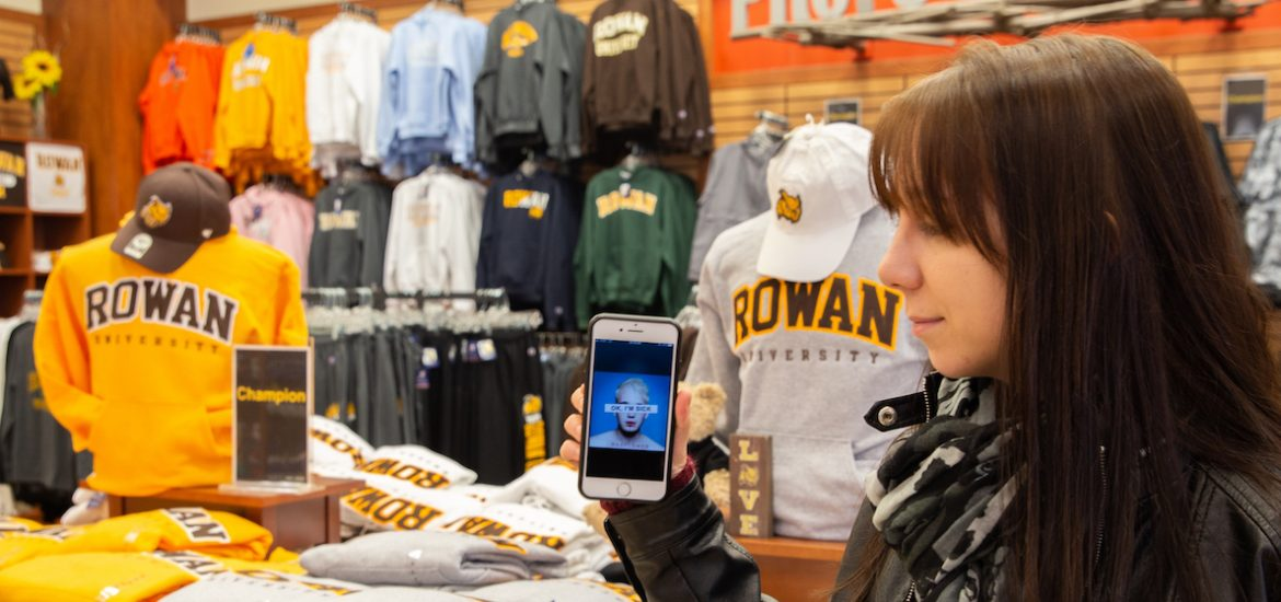 Jen Green stands in the Rowan University bookstore, looking toward her phone with the Badflower album cover OK I'm Sick