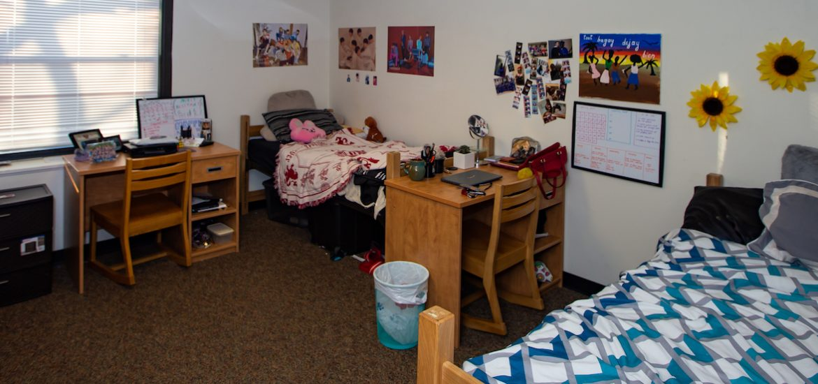 Wide view of students' dorm with two beds, two desks, and a window with its blinds down