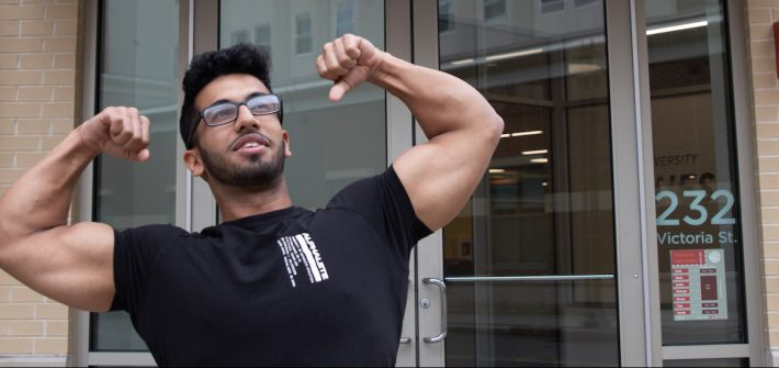 Young male student flexing in front of glass doors