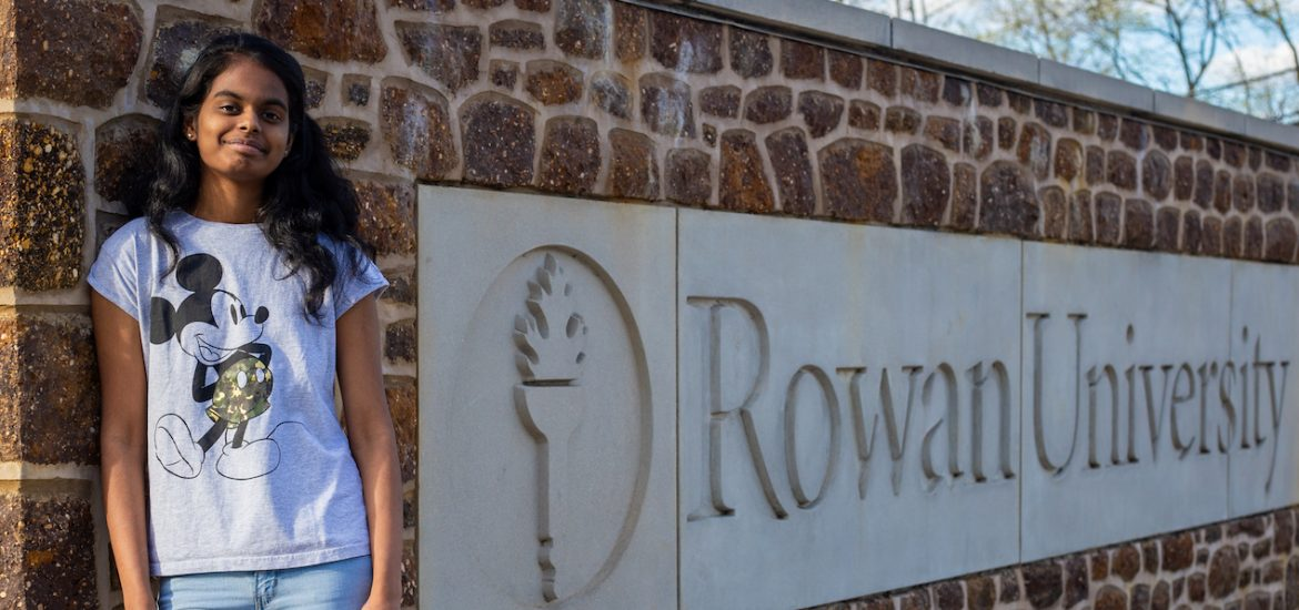 Student outside at Rowan University brick sign out front of Holly Pointe