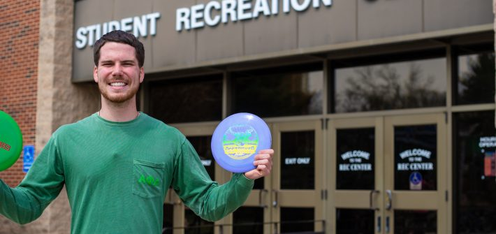Austin out front of the Rec center holding frisbees up outside