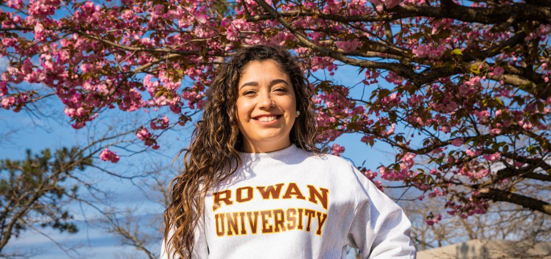 student Allison outside of cherry blossom tree in Rowan hoodie