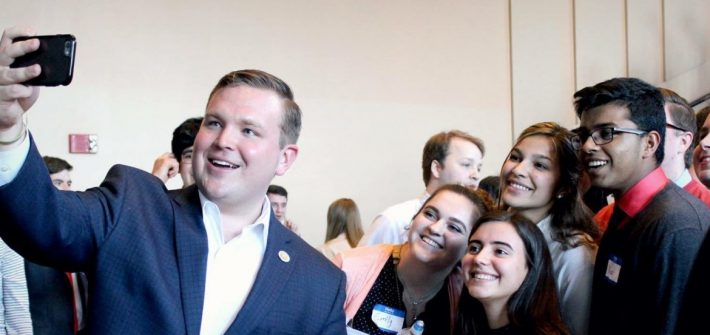 Rowan University alumnus Bill Moen taking a selfie with supporters at a political event.