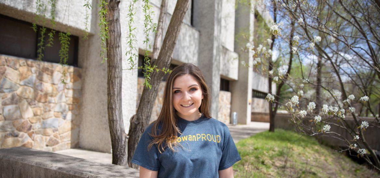 A Rowan University student wearing a #RowanProud shirt stands outside James Hall