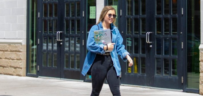 Shaylin Heller, public relations major at Rowan University, walks past the book store holding her laptop and wearing sunglasses