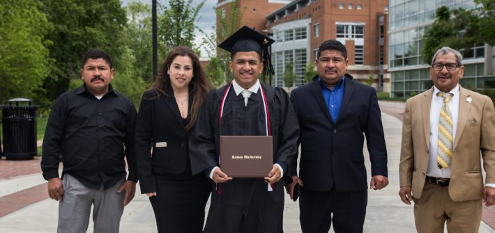 Edwin, in his cap and gown, stands next to his four family members outside Savitz Hall