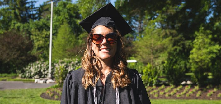 Allyson stands in her cap and gown on the Bunce Green