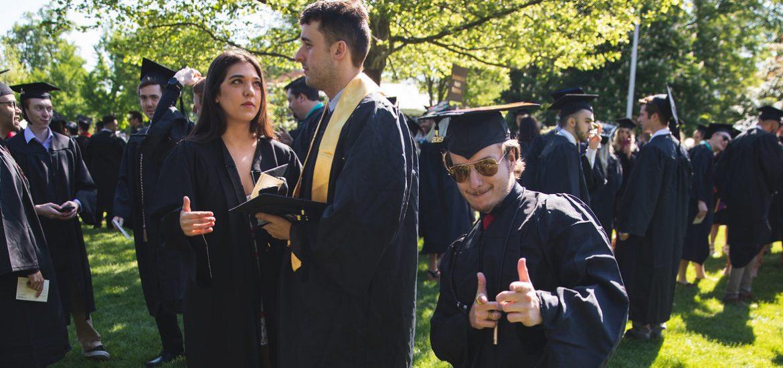 Radio/Tv/Film graduate poses in his black cap and gown.