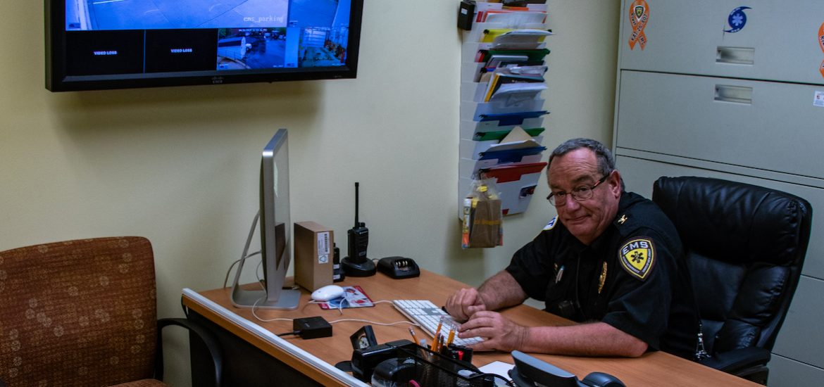 Rowan EMS employee sitting at his desk working diligently on a Mac computer