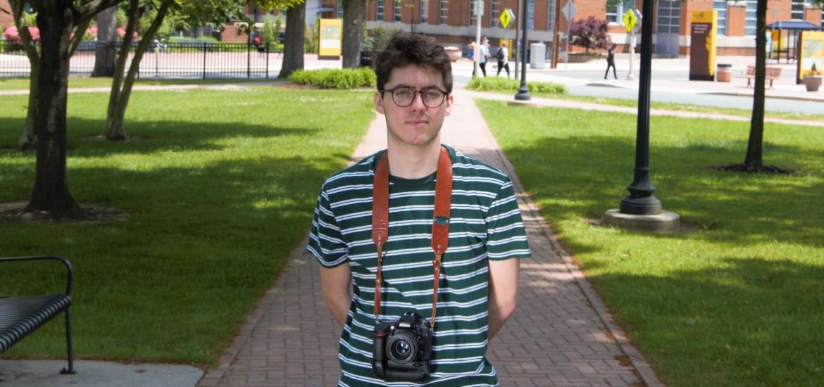 Chad, standing in the gradd of bunce hall with a camera
