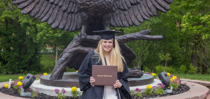 Cheyenne wears her graduation gown, posing with Rowan University diploma holder in front of owl statue